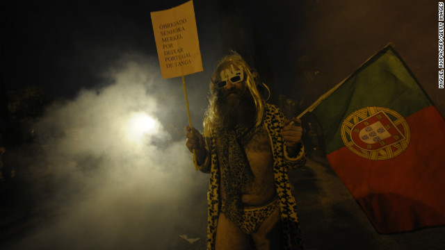 "A man holds a placard reading ""Thanks Mrs. Merkel for leaving Portugal in the buff"" during a protest against the visit of the German chancellor in Belem, near Lisbon."