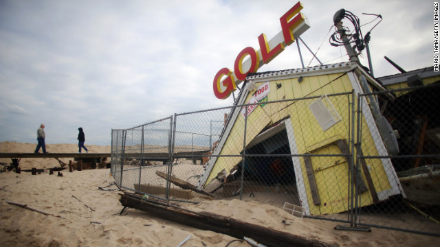People walk past a destroyed miniature golf attraction Wednesday in Point Pleasant, New Jersey.