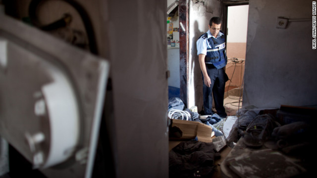 Israeli police inspect an apartment building hit by a rocket fired by Palestinian militants in Kiryat Malakhi on Thursday. At least three Israelis were killed and four were wounded, an Israeli police spokesman said.