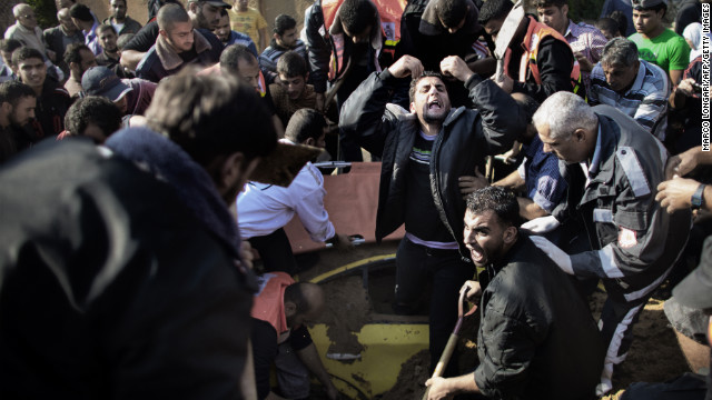 A Palestinian pleads for help as he and others try to save a man trapped under his car after an Israeli air raid Thursday, November 15, in northern Gaza.