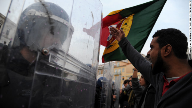 Riot police officers face protesters during a demonstration outside the Portuguese Parliament in Lisbon on November 14, 2012 during a general strike.