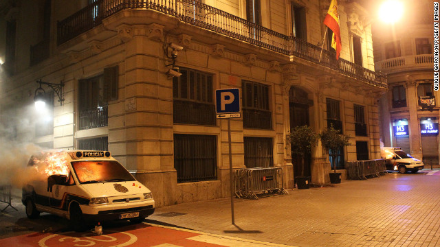 Police vehicles burn close to a Barcelona, Spain, police station Wednesday.