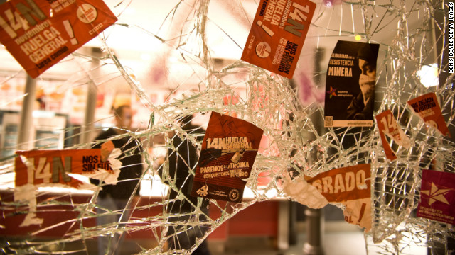 Trade union stickers cover the broken window of a Madrid restaurant after a demonstration Wednesday.