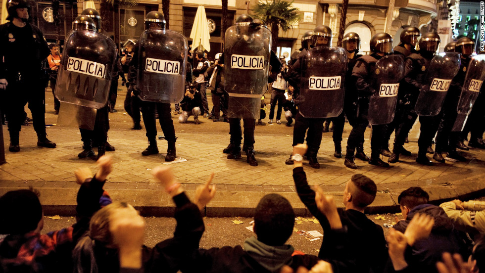 Protesters sit down in front of police Wednesday, November 14, in Madrid, Spain. Demonstrators marched against sweeping austerity measures and high unemployment throughout Europe on Wednesday.