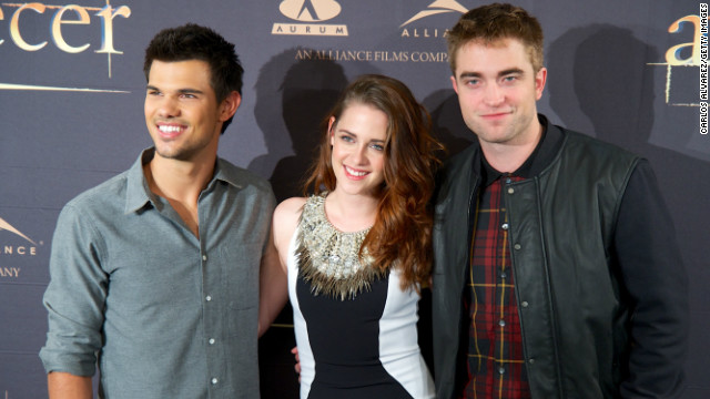 "Massive international fame brings about haircuts, apparently. The starring trio, Taylor Lautner, left, Kristen Stewart and Robert Pattinson, embrace Thursday, November 15, for ""Breaking Dawn -- Part 2's"" Madrid photo call."