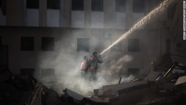 Palestinian firefighters try to extinguish a fire at the Civilian Affairs branch of the Ministry of Interior on Friday, November 16.