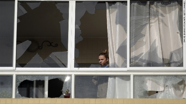 An Israeli woman looks out from an apartment building in Ashdod, Israel, damaged by a rocket fired by Palestinian militants on Friday.