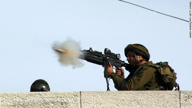 An Israeli soldier fires a tear gas canister toward Palestinian stone throwers on a road mainly used by Israeli settlers in the West Bank village of Beit Omar on Friday.