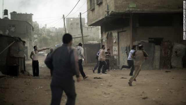 Palestinians run for cover after an Israeli airstrike hits Gaza City on Friday.