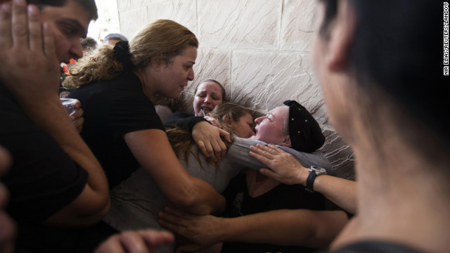 Relatives of Itzik Amsalam, who was killed Thursday in Kiryat Malakhi, Israel, mourn during Friday's funeral.