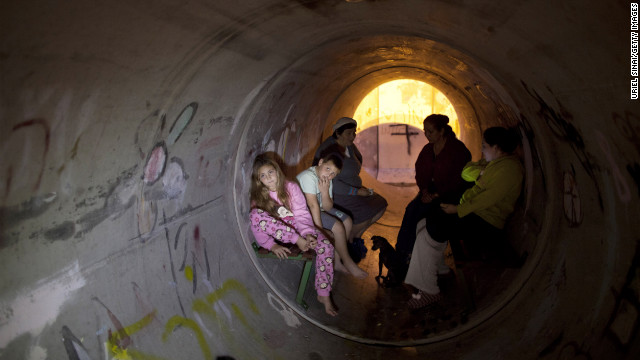 Israelis take cover in a pipe used as a bomb shelter, after a rocket was launched from the Gaza Strip on Thursday, November 15 in Kiryat Malachi, Israel. Rockets and shells crisscrossed between Israel and Gaza on Thursday as Palestinian militants continued rocket attacks on Israeli civilians and Israel pounded what it called terror sites.
