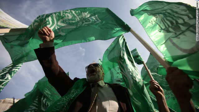 Palestinian protesters hold up the Hamas flag during a rally Friday in the West Bank city of Ramallah.