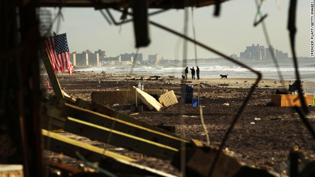 People walk along a beach in the heavily damaged Rockaway neighborhood in the Queens borough of New York on Friday, November 16.