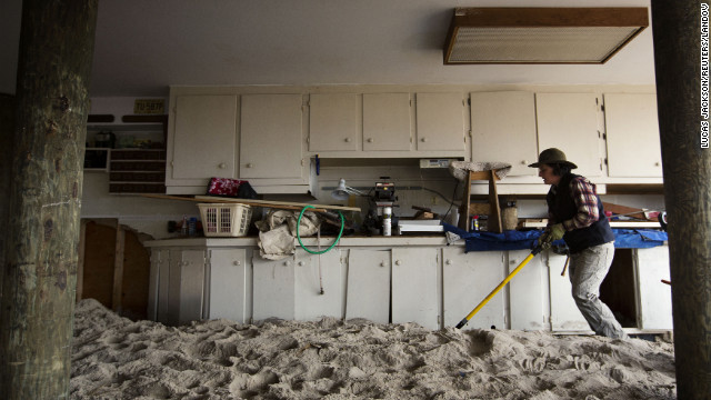 Amy Neukom works to remove sand from her parents' house in Mantoloking, New Jersey, on Friday -- a result of Superstorm Sandy.