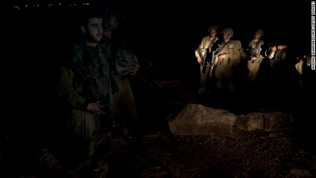 Israeli soldiers stand guard while explosives experts examine the site where a rocket fired from the Gaza Strip landed near the Jewish settlement of Gush Etzion in the village of Kisan, south of Bethlehem on Friday.