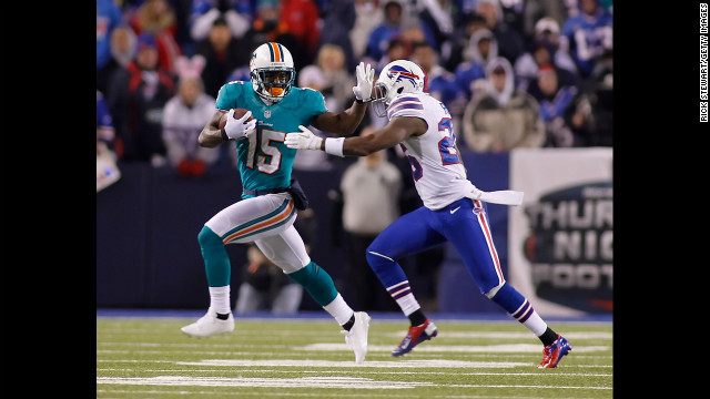 Davone Bess, left, of the Miami Dolphins stiff-arms Justin Rogers of the Buffalo Bills on Thursday.