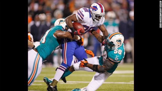 C.J. Spiller of the Buffalo Bills runs against Cameron Wake, left, and Karlos Dansby of Miami.
