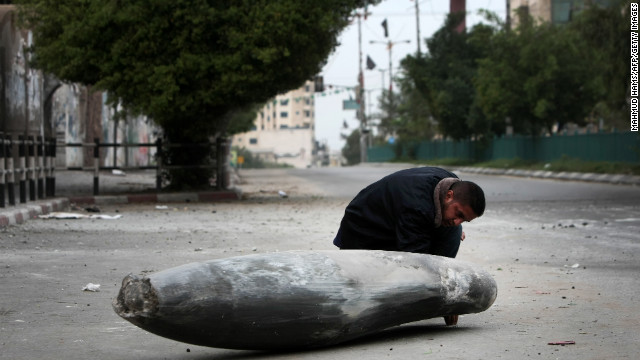 A Palestinian Hamas policeman looks at an Israeli rocket in the street in Gaza City on Saturday.