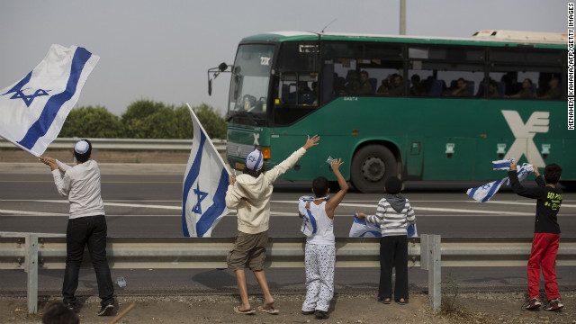 Israeli children wave their national flag Saturday as they greet a bus carrying soldiers on a road leading to the Israel-Gaza border near the southern Israeli town of Ofakim.