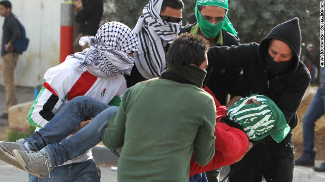 An injured student from the University of Birzeit is carried away Saturday, November 17, during clashes with Israeli soldiers as hundreds of students took part in a demonstration against the ongoing Israeli military offensive on the Gaza Strip in the Israeli occupied West Bank town of Betunia. Israeli strikes on Gaza killed 10 Palestinians and destroyed the Hamas government headquarters.