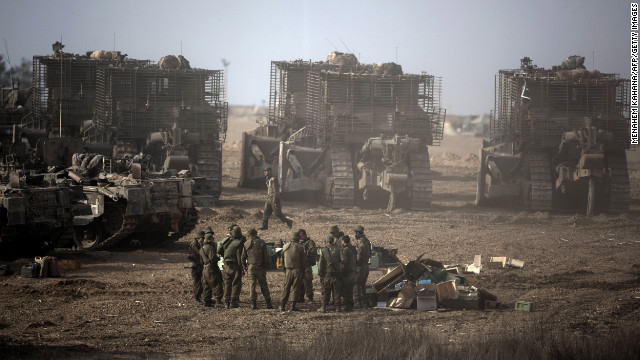 Israeli soldiers gather next to their armored bulldozers stationed on Israel's border with the Gaza Strip on Saturday, November 17. Israeli air strikes destroyed the cabinet headquarters of Gaza's Hamas rulers after militants fired rockets at the heart of Israel, which called up thousands more reservists for a possible ground war.
