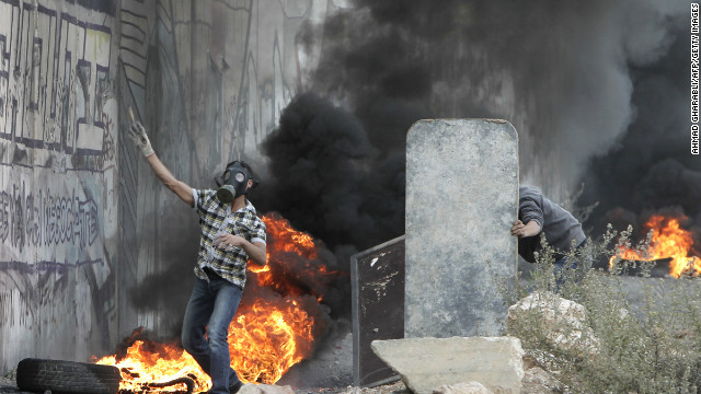 A Palestinian youth takes cover behind a makeshift barrier during clashes with Israeli soldiers on November 17. Israeli strikes on Gaza destroyed the Hamas government headquarters as Israel called up thousands more reservists for a possible ground war.