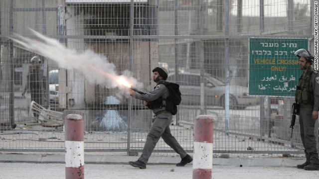 Israeli soldiers fire tear gas toward strone throwers demonstrating against the Israeli military offensive on the Gaza Strip at the Qalandia checkpoint, in the occupied West Bank, on Saturday. Israeli strikes on Gaza destroyed the Hamas government headquarters as Israel called up thousands more reservists for a possible ground war.