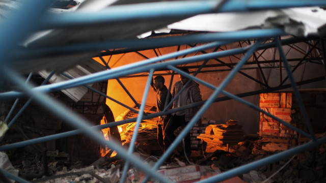 Palestinians walk amid the debris of a burning factory near the house of Ezzedine Haddad, commander of the armed wing of the Hamas movement, after it was destroyed during an Israeli air strike on Gaza City on Saturday.