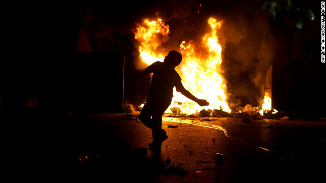 A Palestinian demonstrator throws stones in front of the headquarters of the Palestinian security forces in the West Bank city of Jenin on Sunday, November 18, during a protest against Israel's ongoing military operation in Gaza.