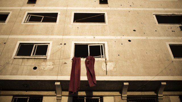 Cloth hangs from a window of a building damaged during Israeli air strikes on Gaza City on Sunday.