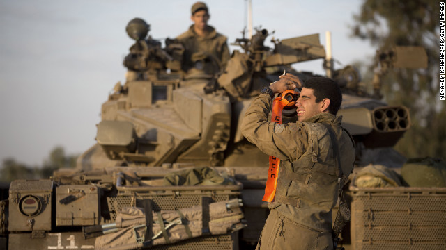 An Israeli soldier from a tank squadron adjusts the tank barrel at an Israeli army deployment area on Sunday.