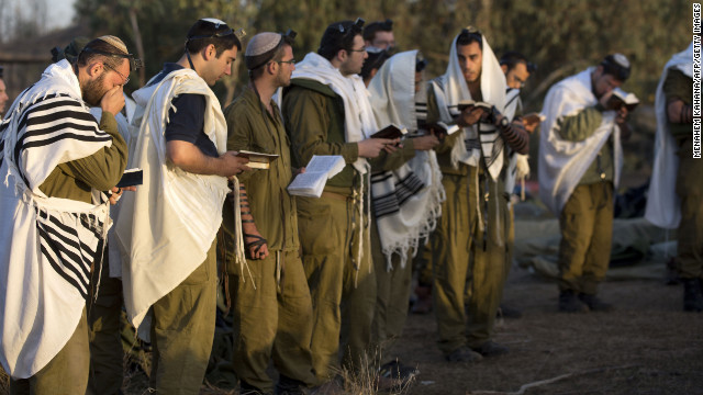 Israeli soldiers wearing prayer shawls conduct morning prayers Sunday at an Israeli army deployment area.