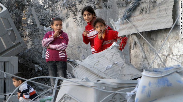 Palestinian children look at damaged buildings following Israeli air strikes Sunday in Rafah.