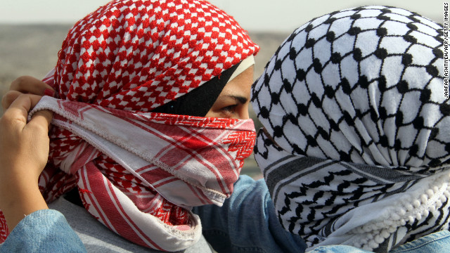 A Palestinian woman helps her friend cover her face with a traditional scarf during clashes at the Hawara checkpoint in the occupied West Bank city of Nablus on Saturday. People rallied against the Israeli military operations.