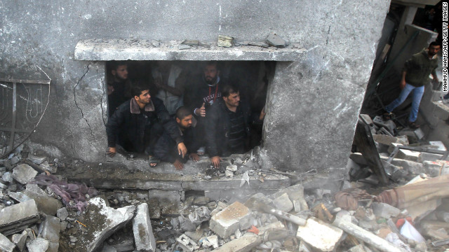 Palestinians search the debris of the home following an Israeli airstrike in Gaza City on Sunday.