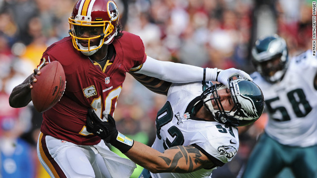 Quarterback Robert Griffin III of the Washington Redskins stiff arms defensive end Jason Babin of the Philadelphia Eagles in the second quarter at FedEx Field on Sunday in Landover, Maryland.