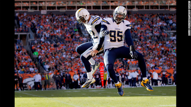 No. 32 Eric Weddle of the Chargers celebrates his 23-yard interception for a touchdown with No. 95 Shaun Phillips of the Chargers against the Broncos in the first quarter on Sunday.