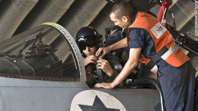 An Israeli pilot adjusts a strap as he sits in the cockpit of a jet at an air force base on Monday.
