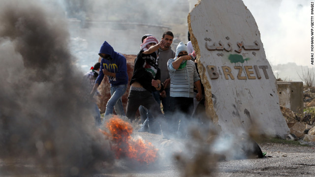 Birzeit University students clash with Israeli soldiers at the Atara checkpoint close to the West Bank university as they protest against Israel's military action on Monday.
