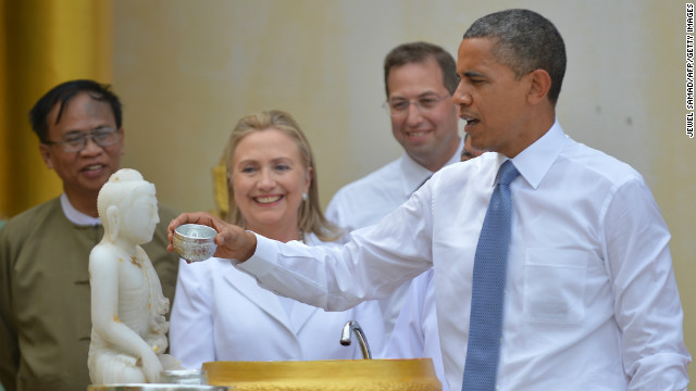 U.S. President Obama performs a ritual as U.S. Secretary of State Hillary Clinton looks on at a visit to the Shwedagon pagoda in Yangon on Monday.