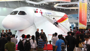 Visitors inspect the C919 prototype at an aviation exhibition during the Zhuhai Airshow