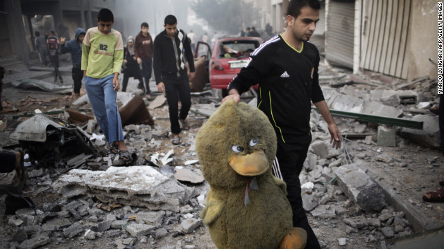 A Palestinian man carries a stuffed toy through a street littered with debris after an air raid on a sporting center in Gaza City on Monday.