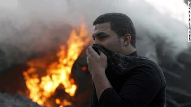 A man covers his nose and mouth as he passes burning debris after Israeli airstrikes in Gaza City on Monday.