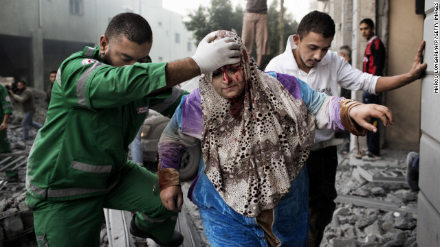 A paramedic helps a Palestinian woman out of her building, which was damaged during an Israeli air raid on a nearby sporting center in Gaza City on Monday. At least 90 Palestinians, including a family of 10, have been killed, officials say.