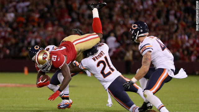 Frank Gore of the San Francisco 49ers tries to leap over Major Wright, center, and Tim Jennings, left, of the Chicago Bears.