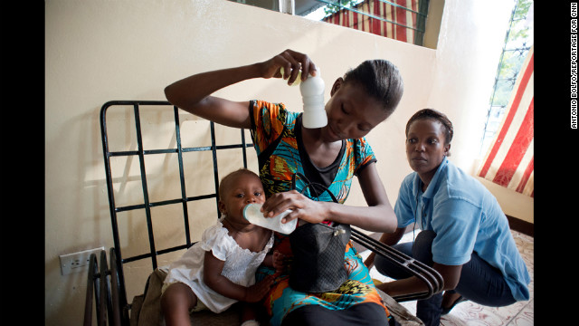 A woman and her baby attend a group meeting at the KOFAVIV center while a employee of the nonprofit looks on. 