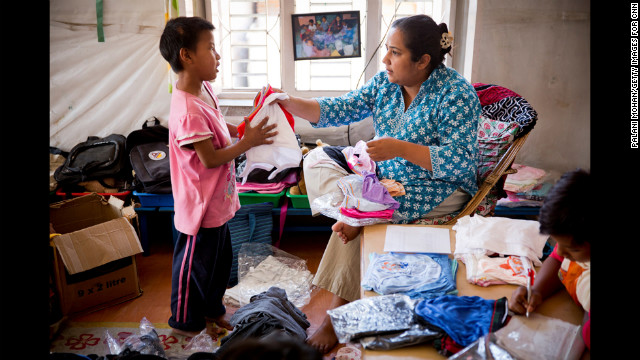 Basnet hands out new clothes to one of the young children she cares for in Kathmandu. The children reciprocate her love by calling her &quot;Mamu,&quot; which means &quot;mommy.&quot;