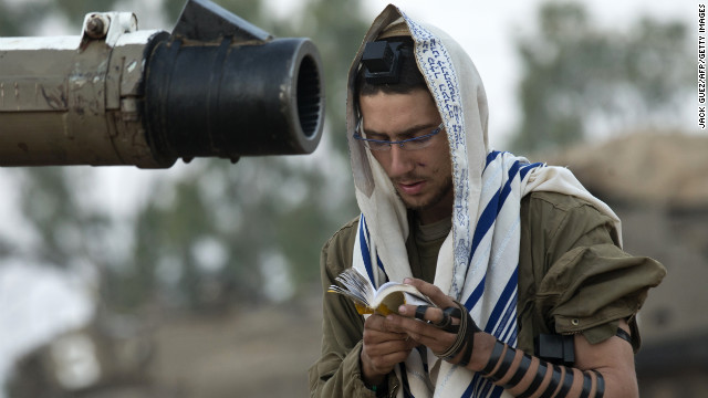 An Israeli soldier reads his morning prayers Tuesday at an Israeli army deployment area near the Israel-Gaza border as they prepare for a potential ground operation in the Palestinian coastal enclave. 