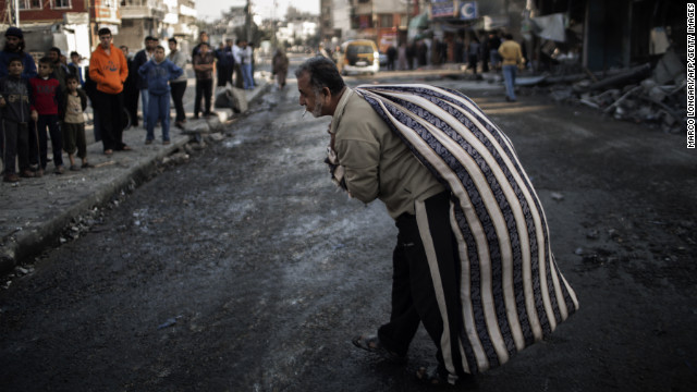 A Palestinian carries a bag of items salvaged from a house destroyed in an Israeli airstrike Tuesday on Gaza City.