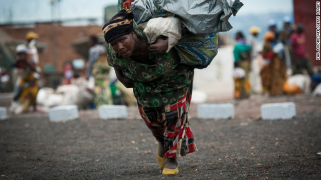 A displaced Congolese woman carries her belongings as she enters a United Nations base in Monigi, 5km from Goma on November 18, 2012.